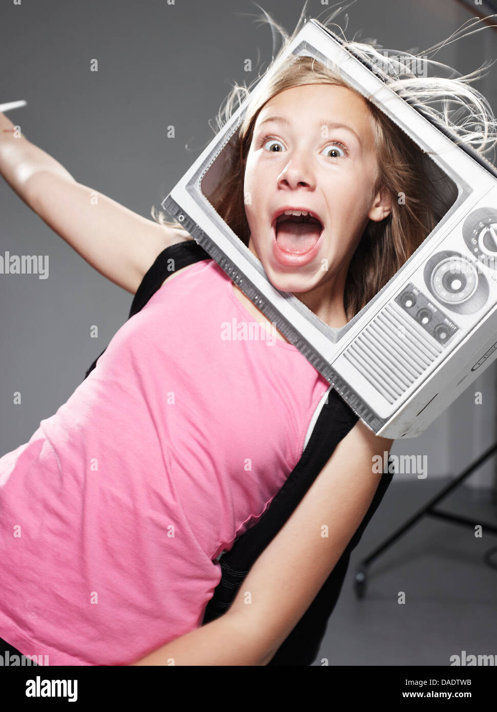 Girl screaming in paper TV against grey background - Stock Image