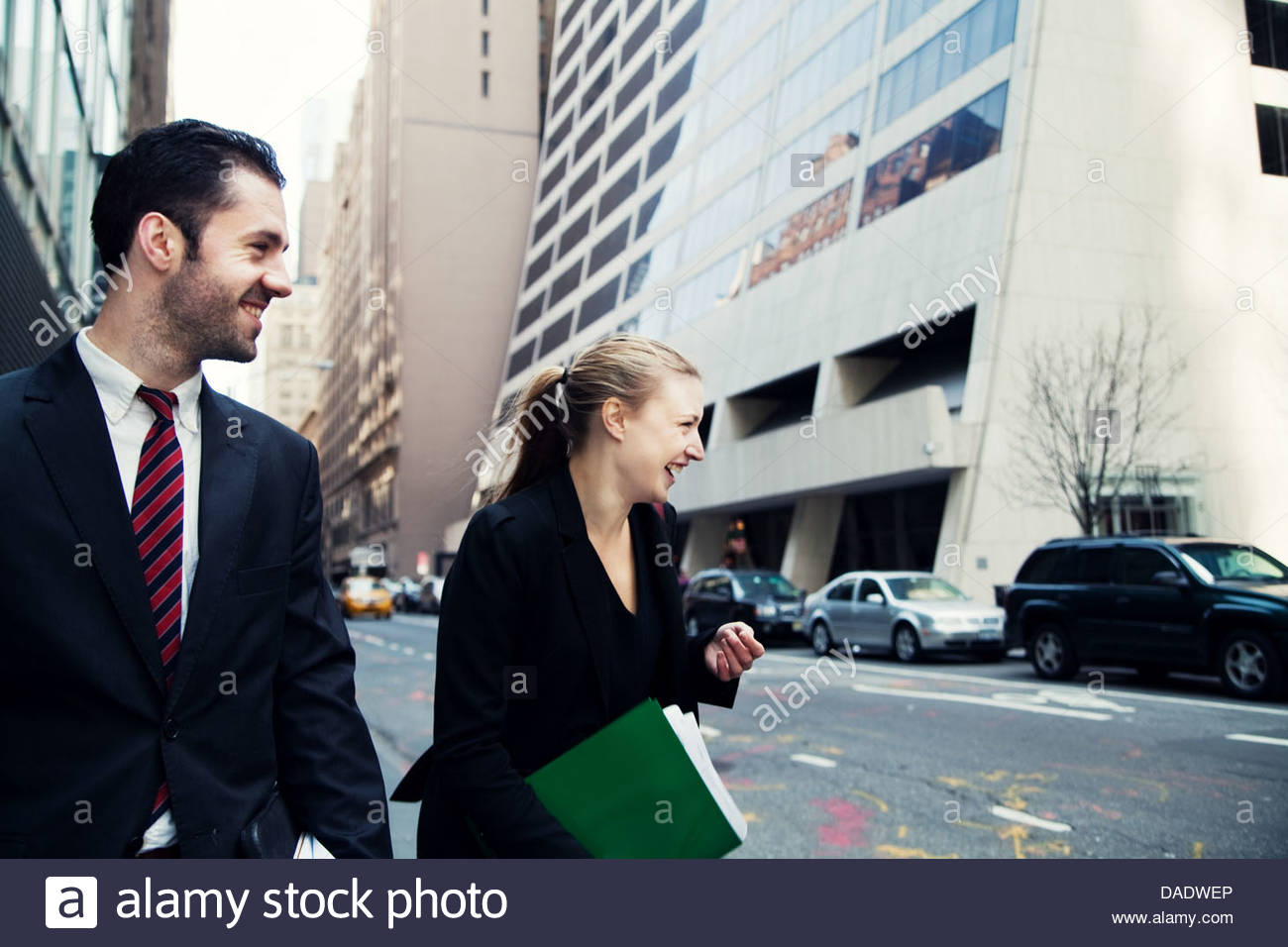 Businessman and businesswoman walking on city street and laughing - Stock Image