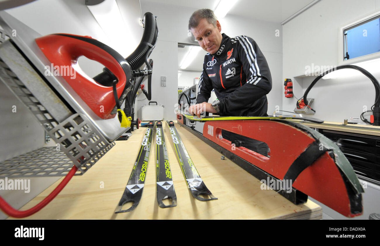 Ski technician Andreas Emslander waxes a ski in the waxing truck, a mobile workshop for the biathlon athletes of - Stock Image