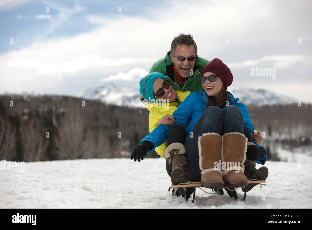 Three friends sitting on sledge in snow Stock Photo