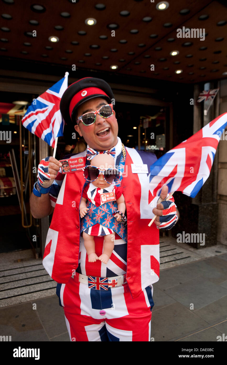 London, UK, A member of staff in Union Jack clothing complete with a Royal baby doll outside the Cool Brittania - Stock Image