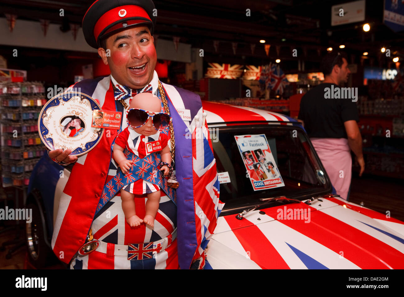 London, UK, A member of staff in Union Jack clothing complete with a Royal baby doll inside the Cool Brittania Souvenir - Stock Image