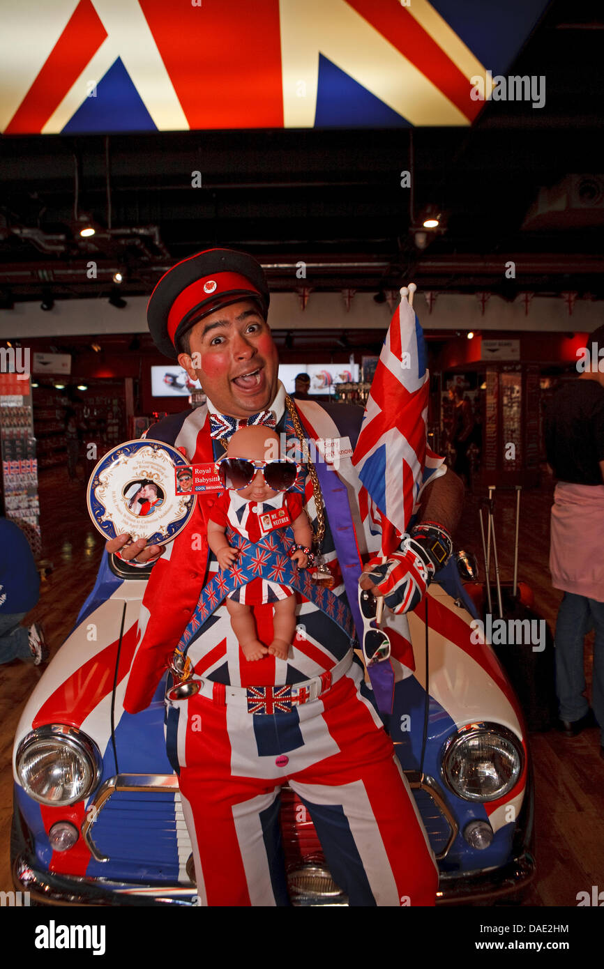 London, UK, A member of staff in Union Jack clothing complete with a Royal baby doll sits on a mini inside the Cool - Stock Image