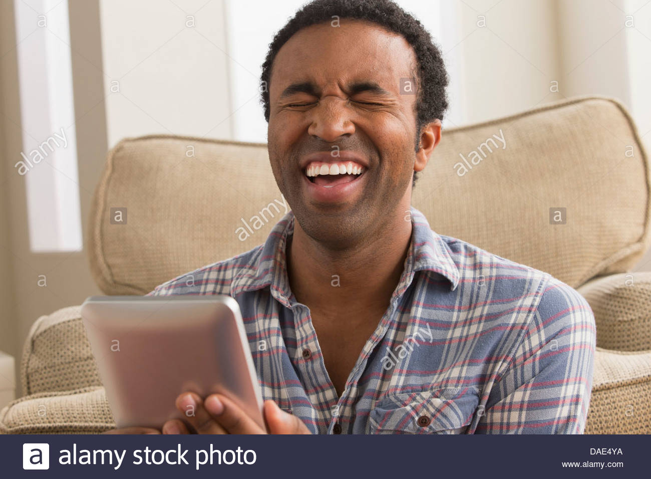 Young man with electronic book, laughing - Stock Image