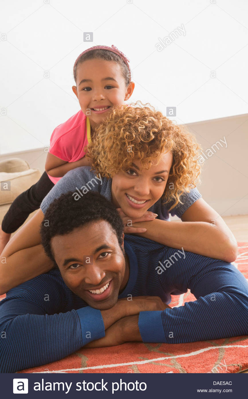Daughter on top of parents, portrait - Stock Image