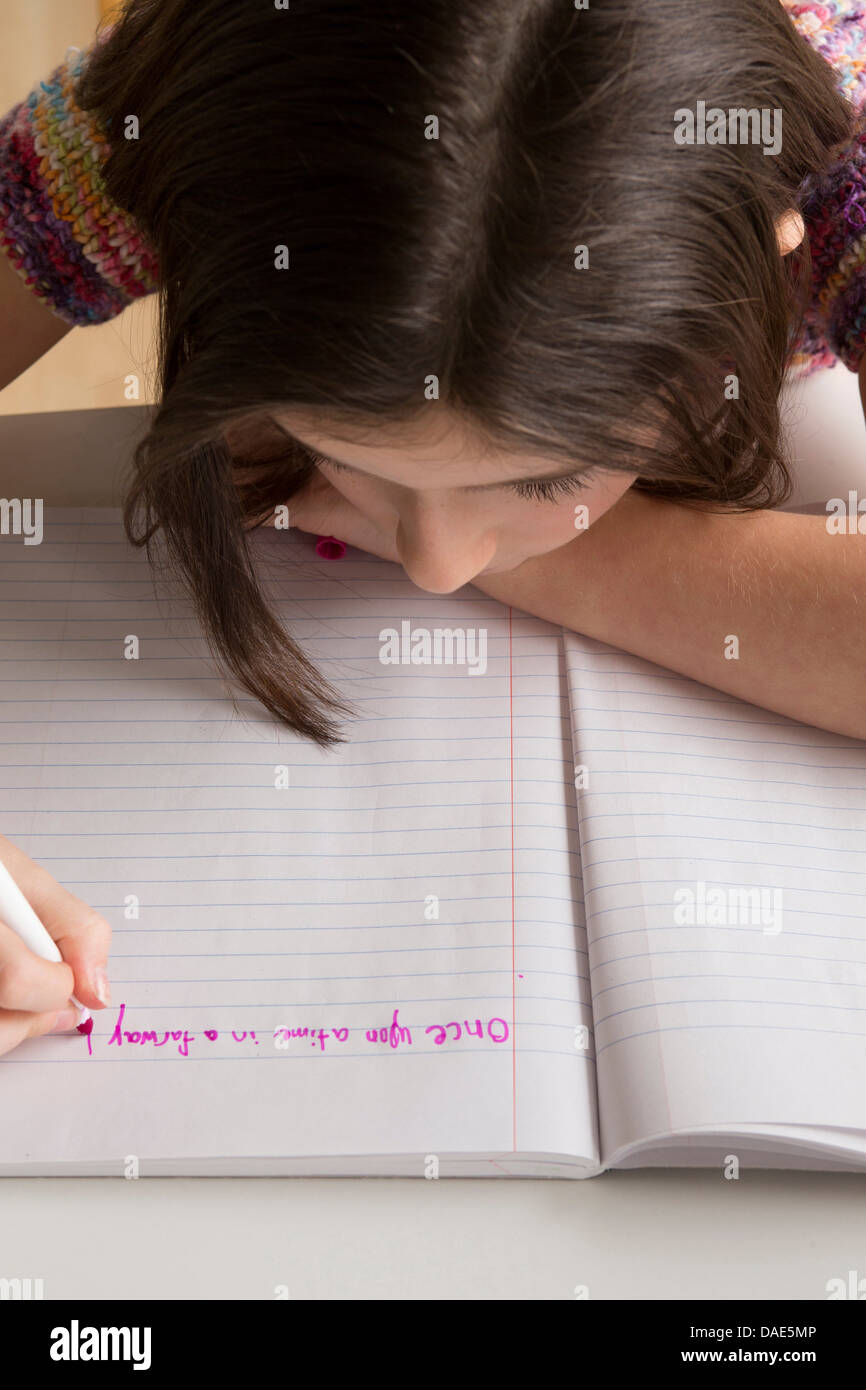 Girl writing in pink felt tip pen in notebook - Stock Image
