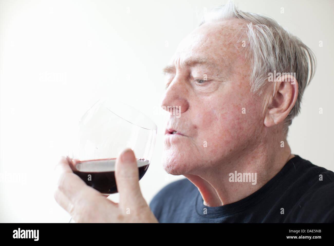 Senior man drinking red wine - Stock Image