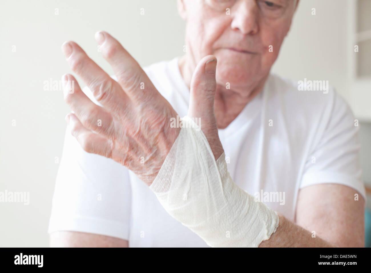 Senior man with bandage on wrist - Stock Image