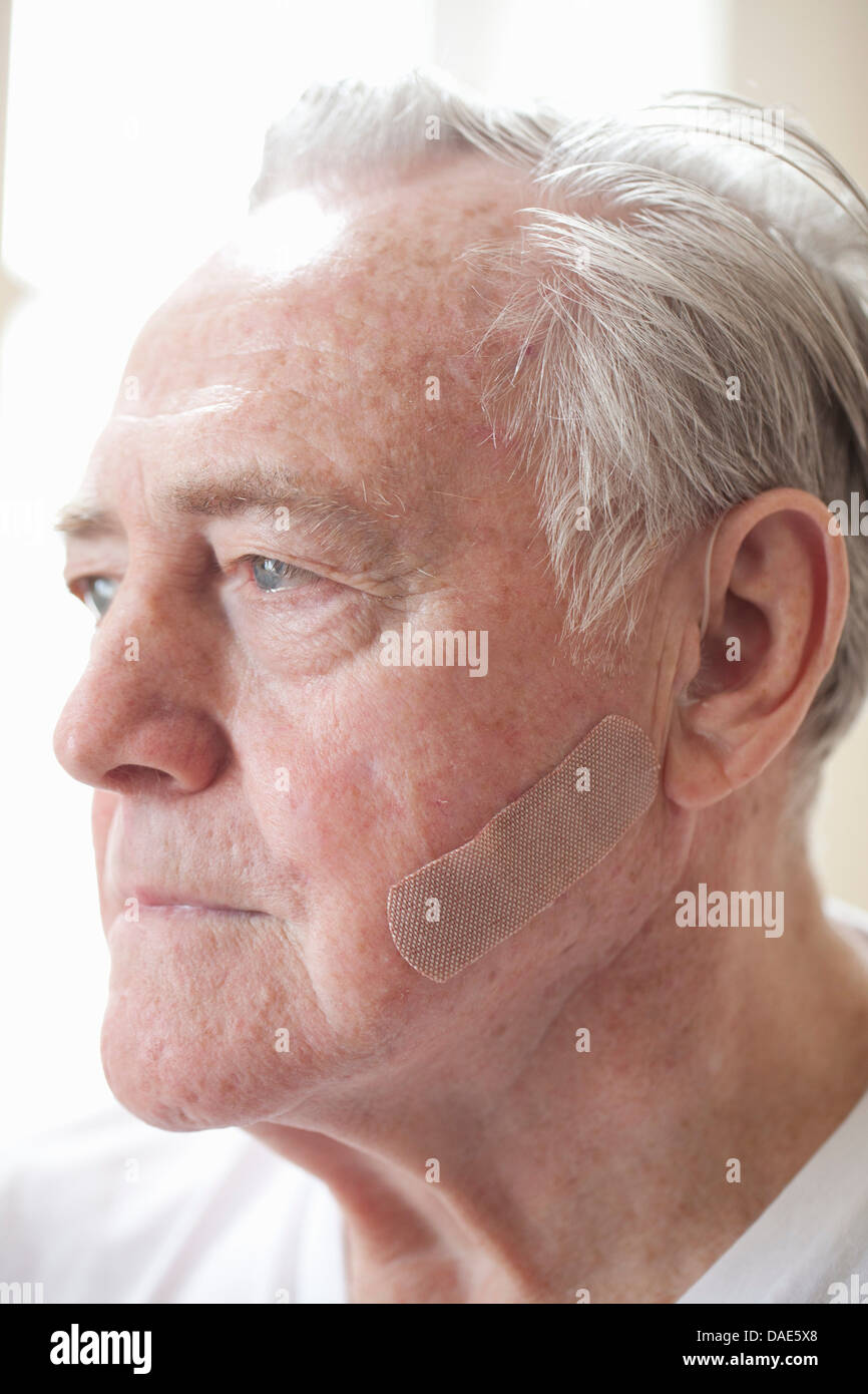Portrait of senior man with adhesive plaster on cheek - Stock Image