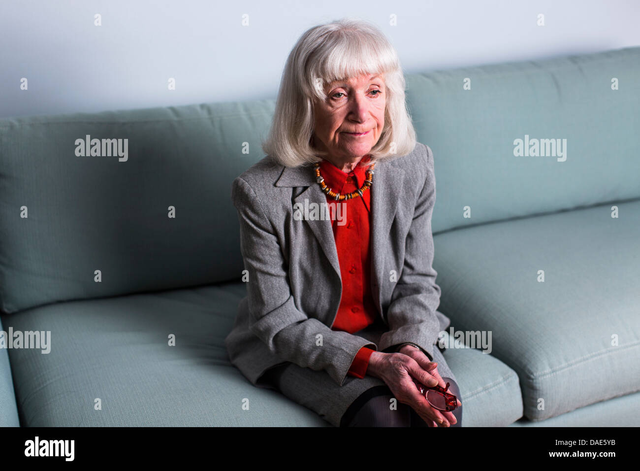 Senior woman sitting on sofa with blank expression - Stock Image