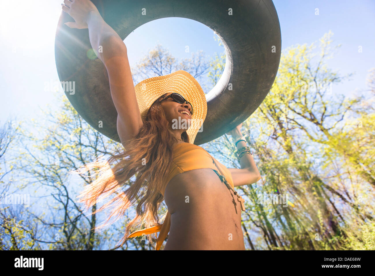 Woman wearing hat and sunglasses carrying inner tube above head - Stock Image