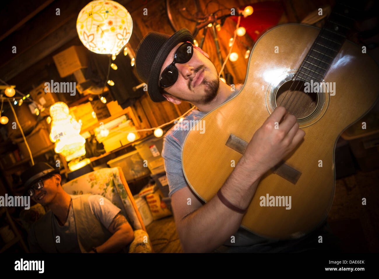 Man wearing hat and sunglasses playing guitar - Stock Image