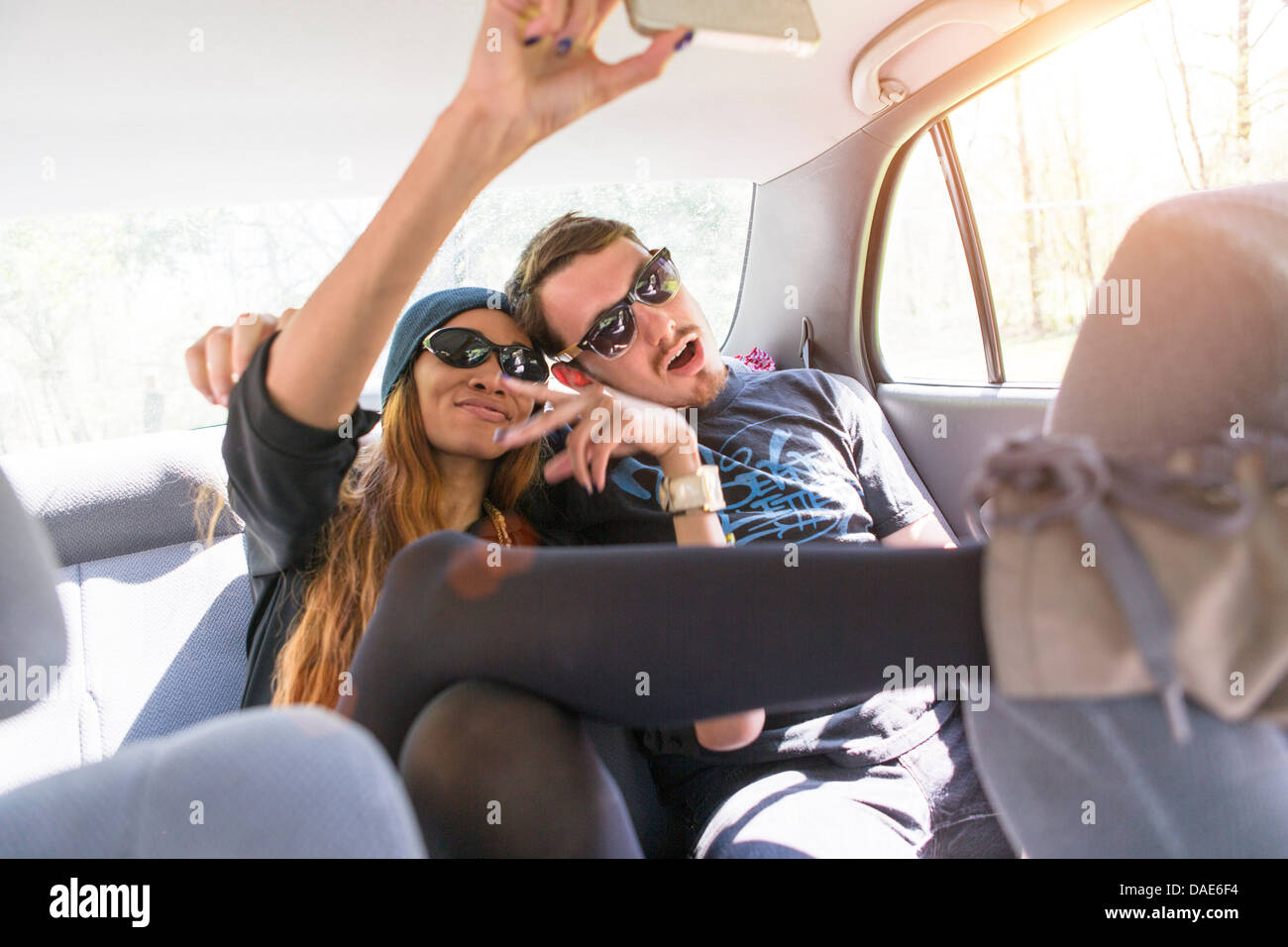 Couple on backseat in car photographing themselves - Stock Image