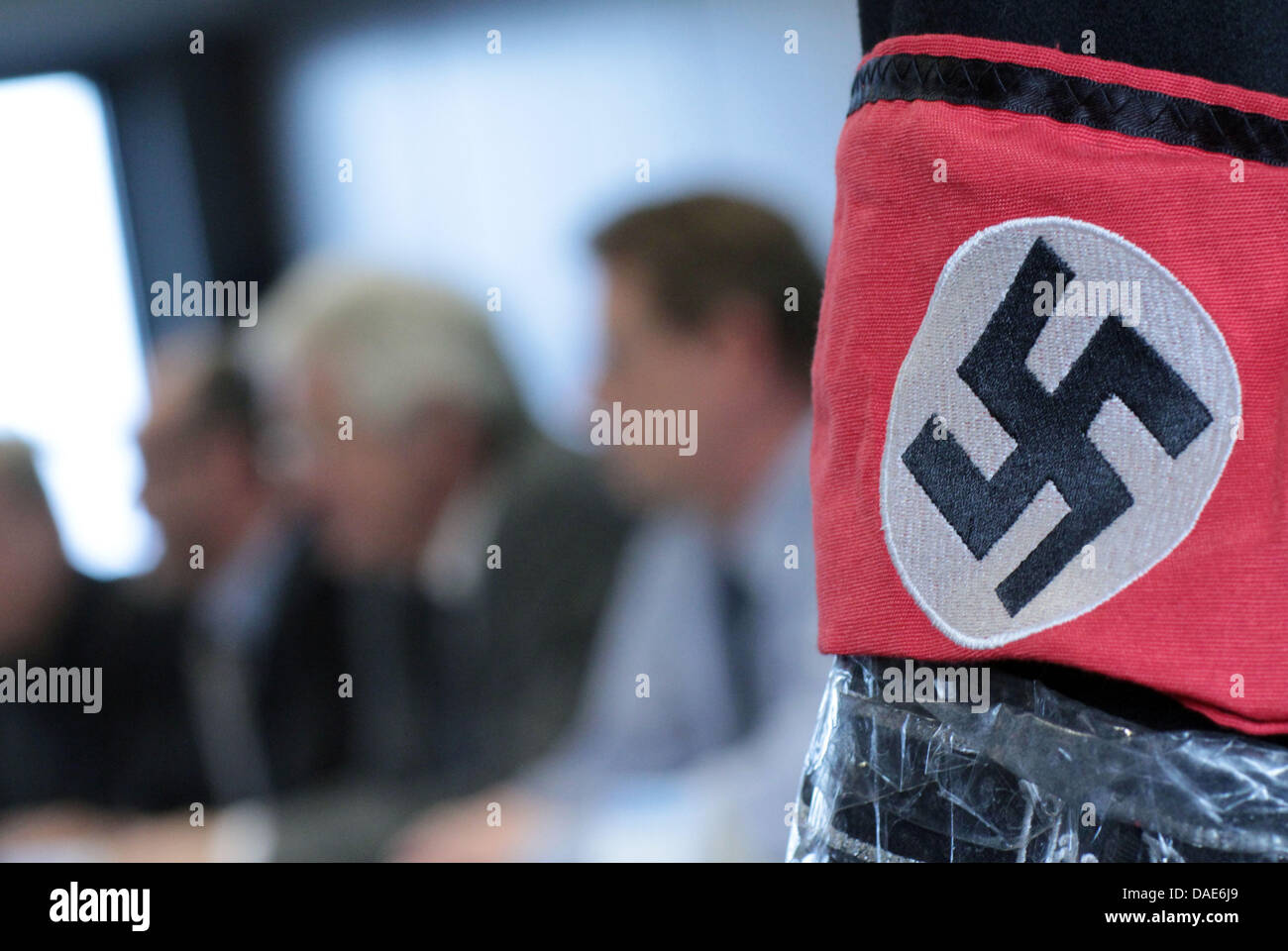 The jacket of the perpetrator with an armband and swastika symbol are presented at a press conference in police - Stock Image