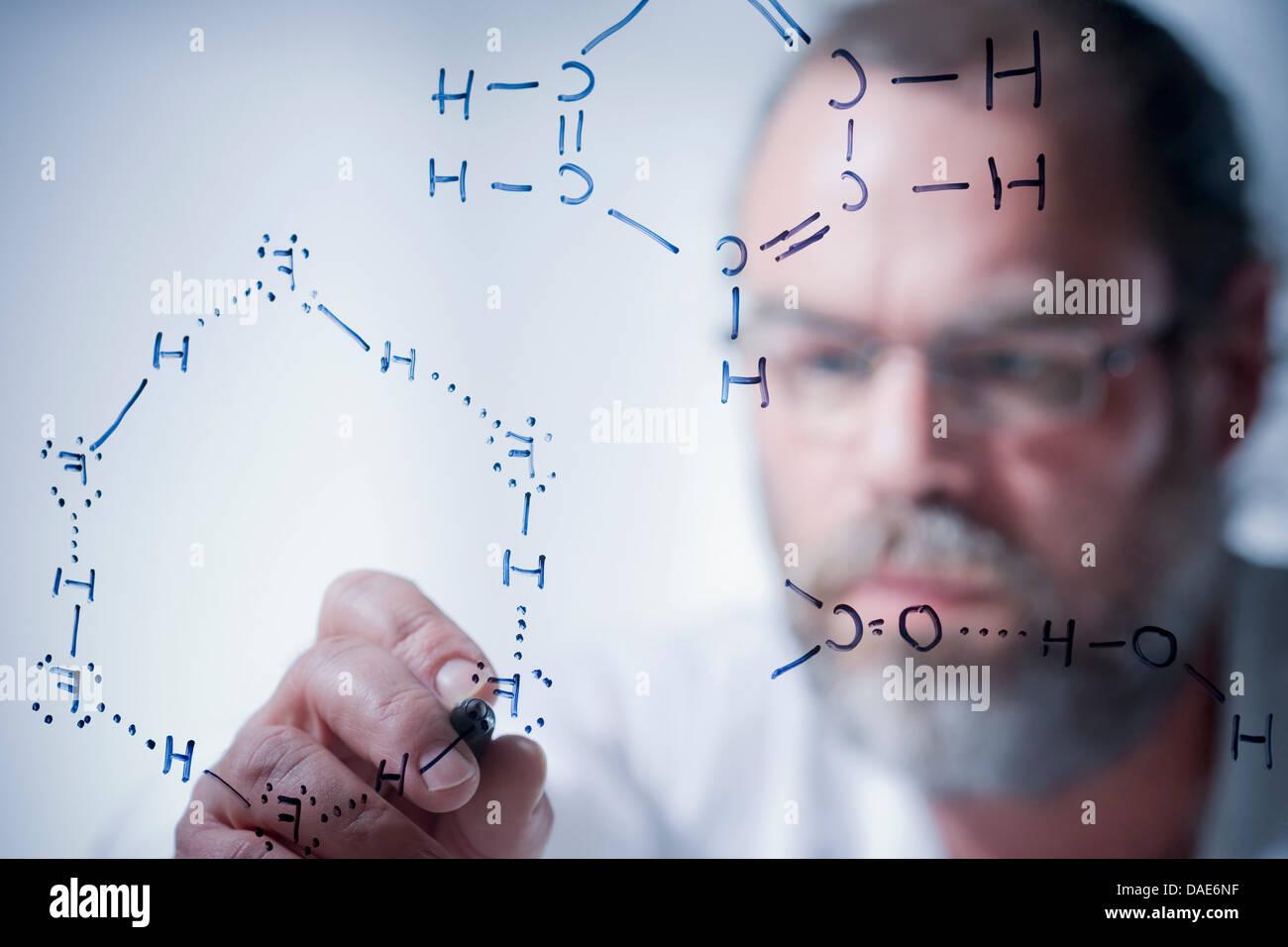 Scientist writing scientific symbols on glass - Stock Image