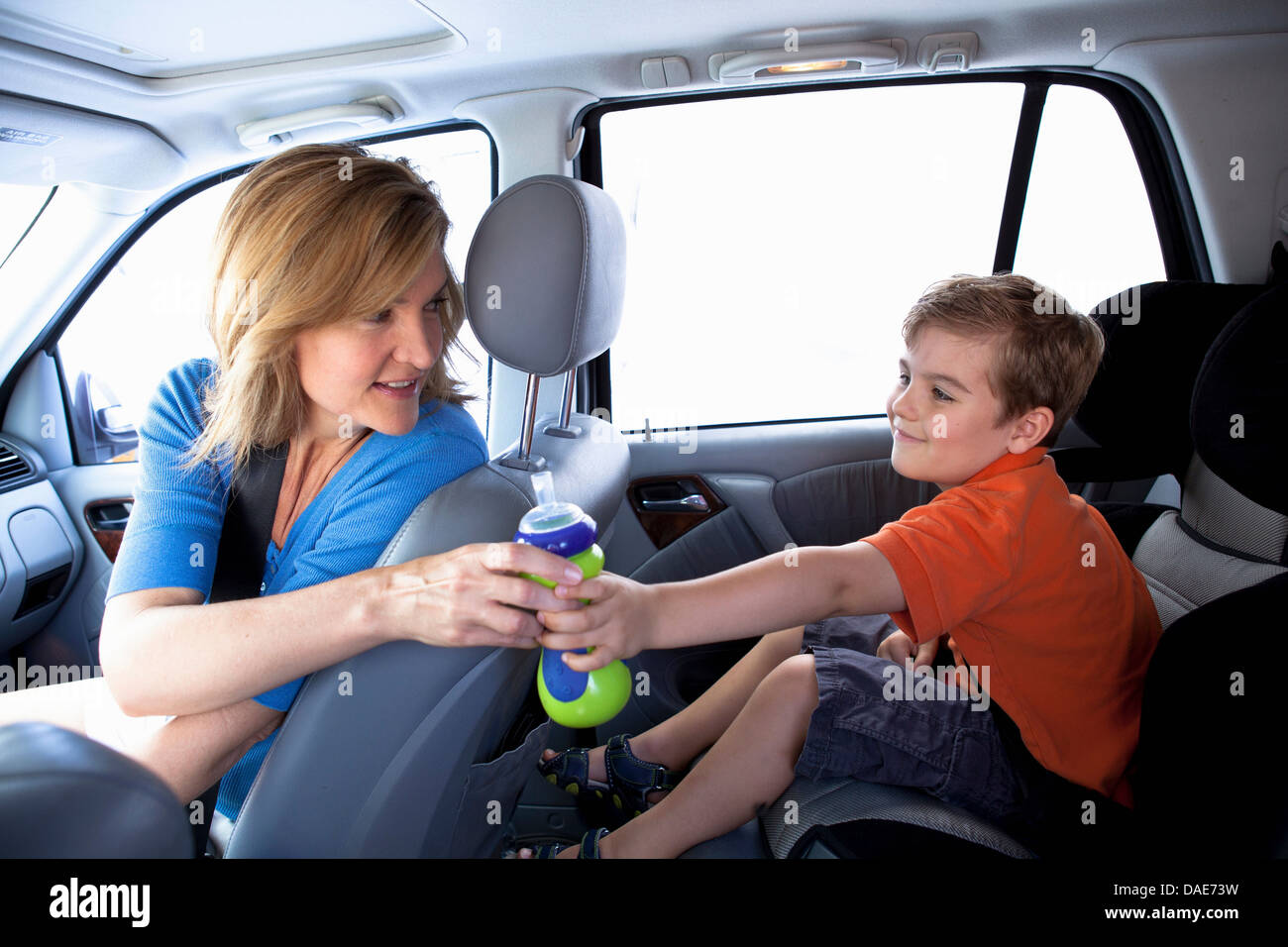 Mother passing bottle to boy in back seat of car - Stock Image