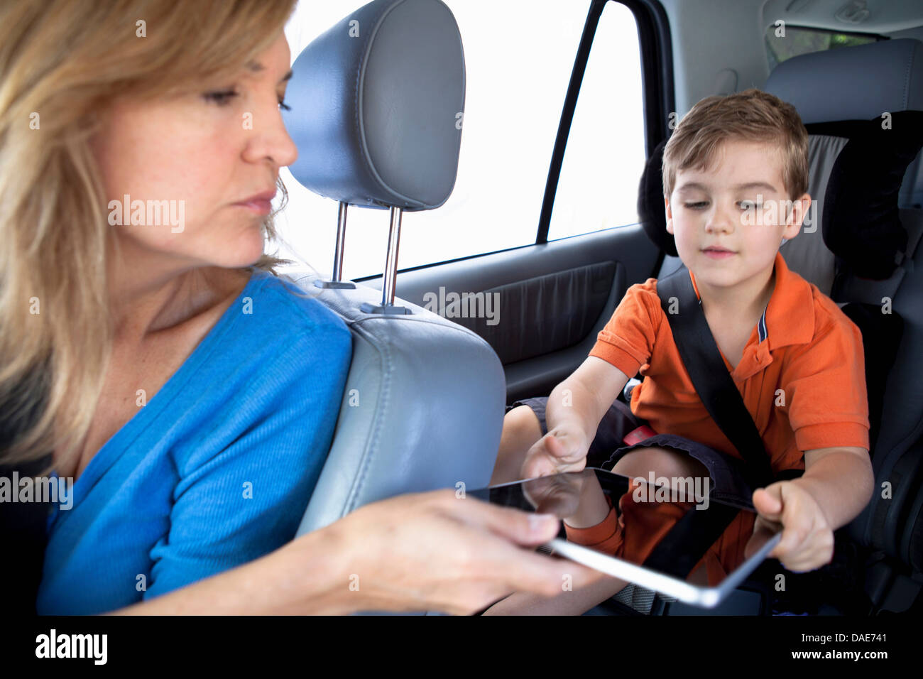 Mother passing digital tablet to son in back seat of car - Stock Image