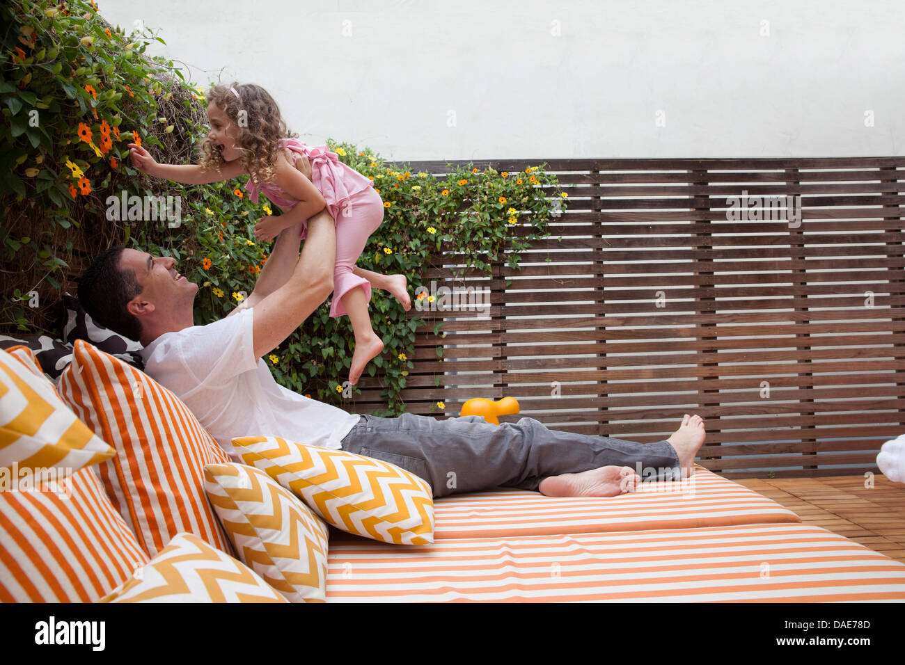 Father lifting daughter in the air - Stock Image