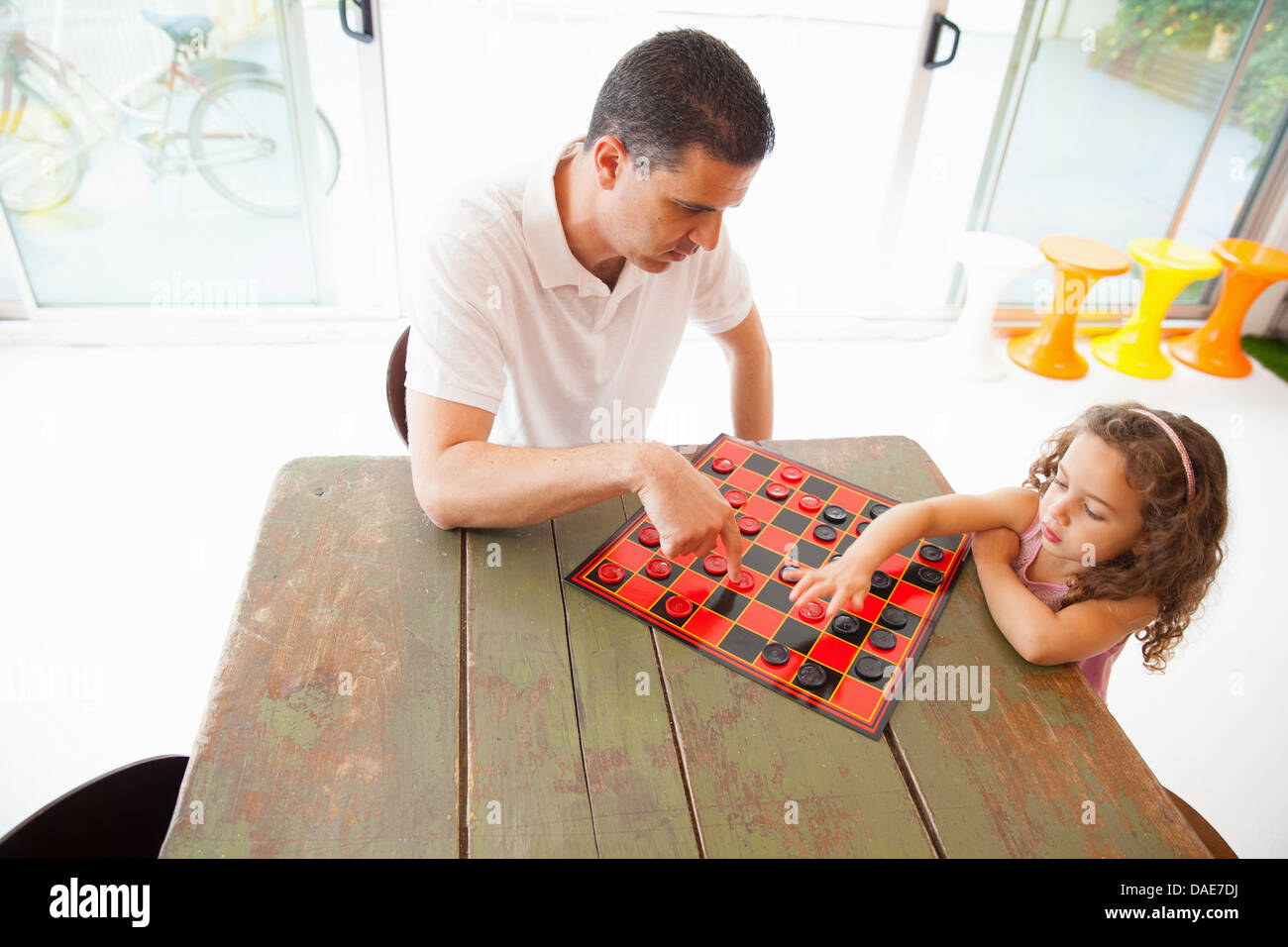 Father and daughter playing draughts - Stock Image