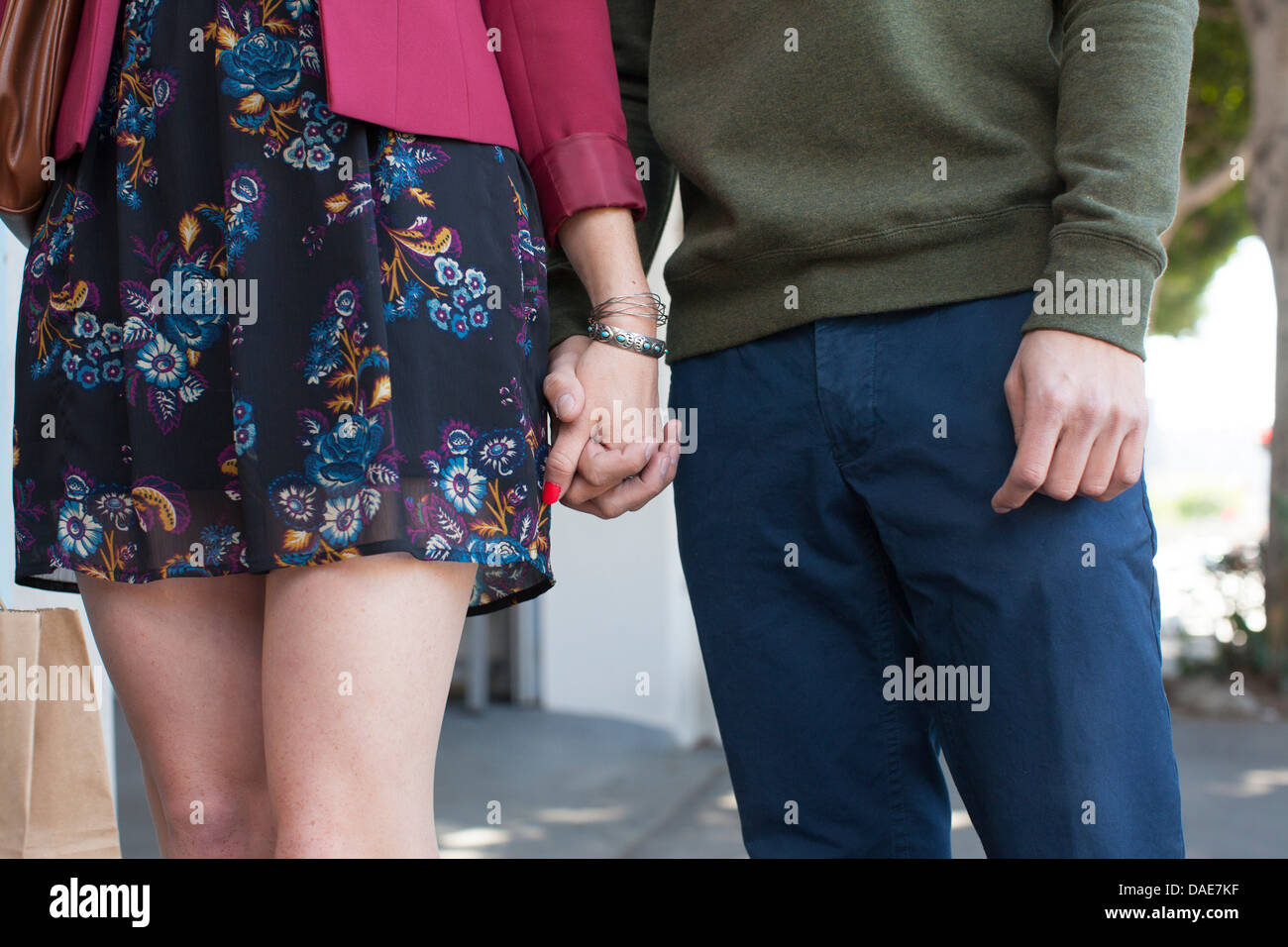 Young couple holding hands, mid section - Stock Image
