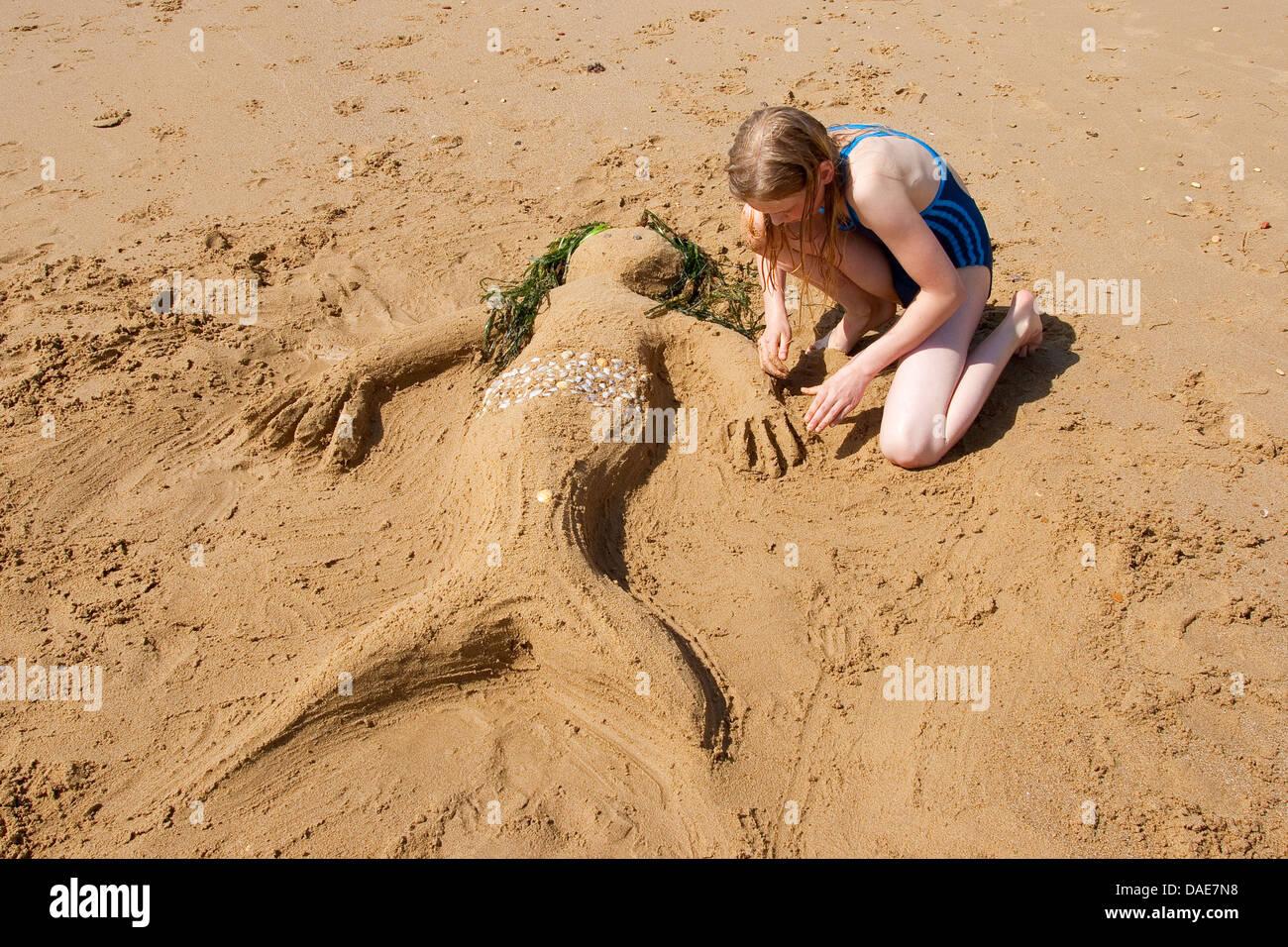 girl creating a mermaid at the mediterrian beach of Sand, seashells, little stones and algae, Italy, Sicilia - Stock Image