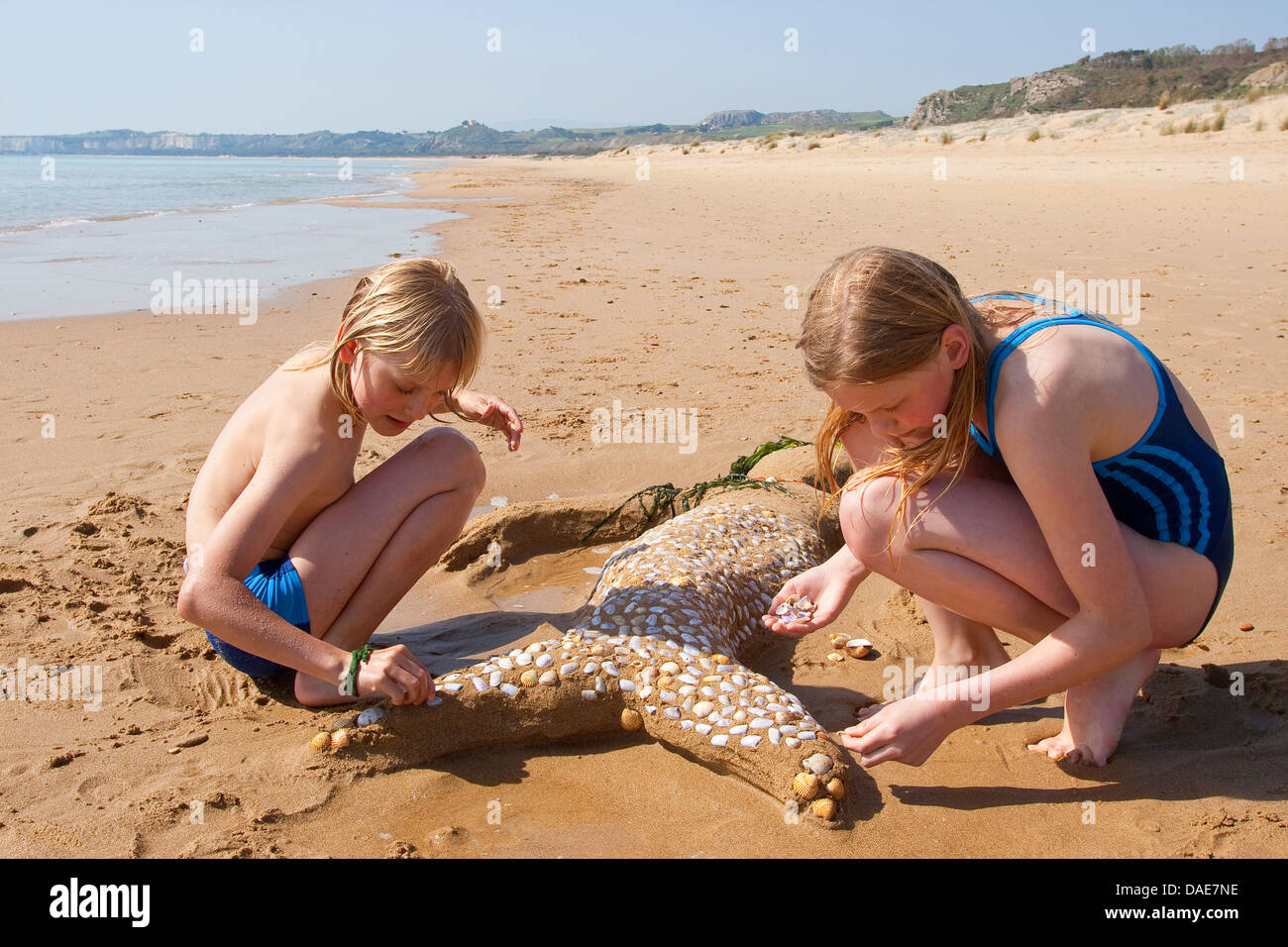two children creating a mermaid at the mediterrian beach of Sand, seashells, little stones and algae, Italy, Sicilia - Stock Image