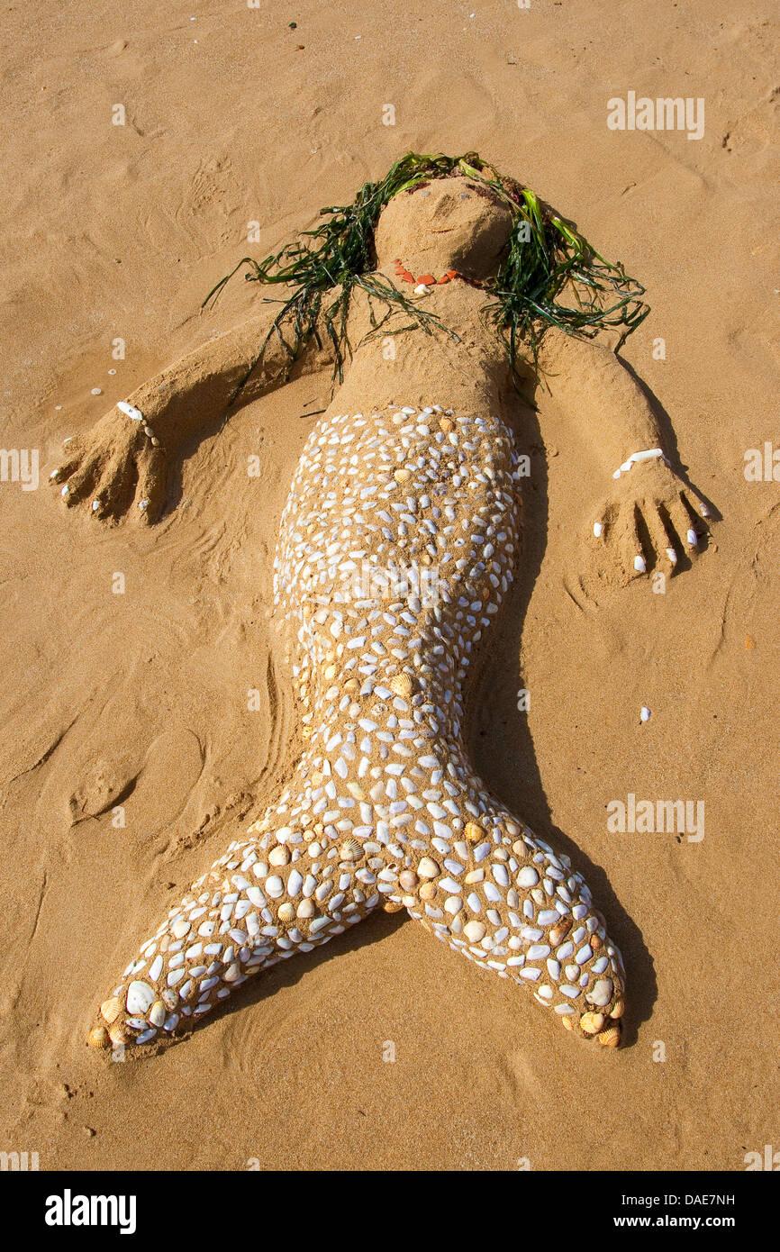 mermaid created of Sand, seashells, little stones and algae at the mediterrian beach, Italy, Sicilia - Stock Image
