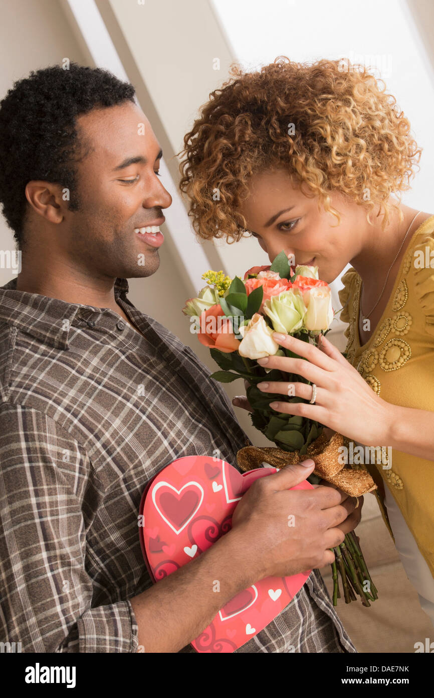 Man giving woman flowers and chocolates on valentines day - Stock Image
