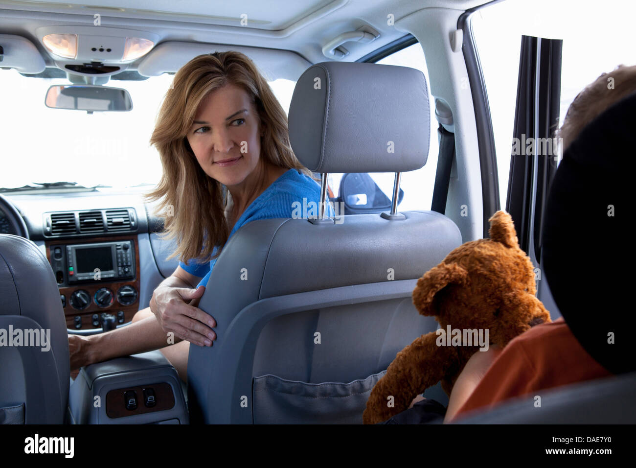 Mother turning around to child in car - Stock Image