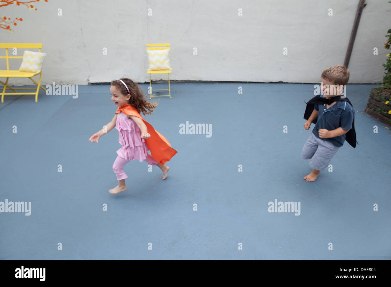 Boy and girl wearing superhero capes playing in back yard - Stock Image