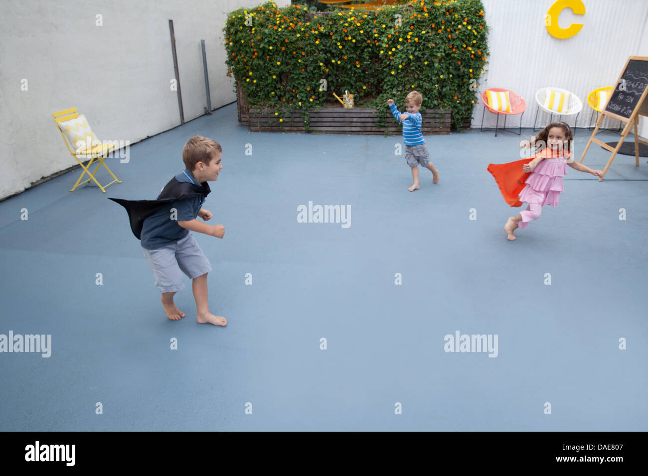 Boys and girl wearing superhero capes playing in back yard - Stock Image