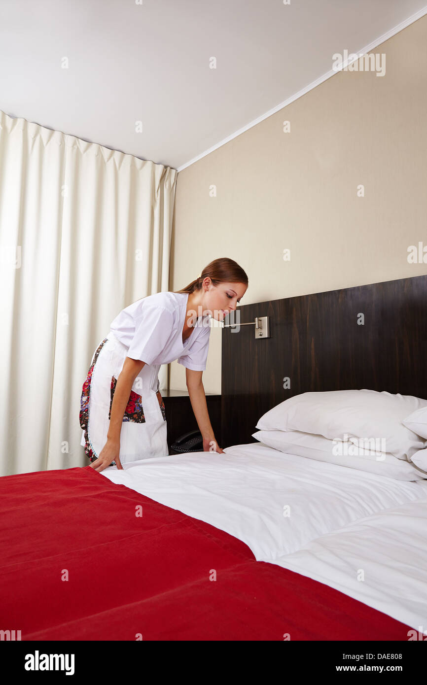 Hotel Room Photography: Young Housekeeping Maid Cleaning Bed In Hotel Room Stock