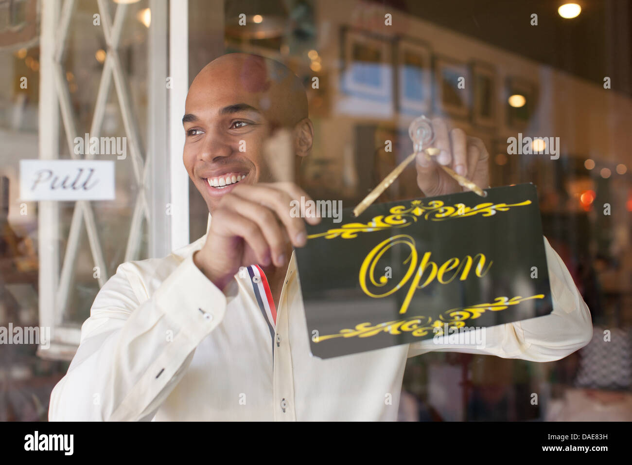 Shopkeeper turning open sign on vintage shop door - Stock Image