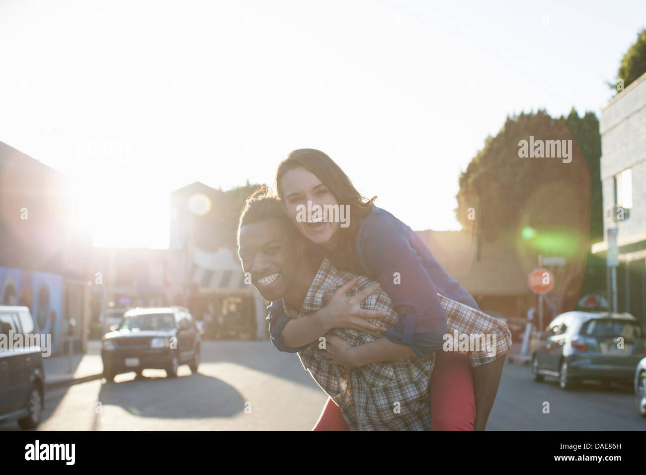Young man giving woman piggy back - Stock Image