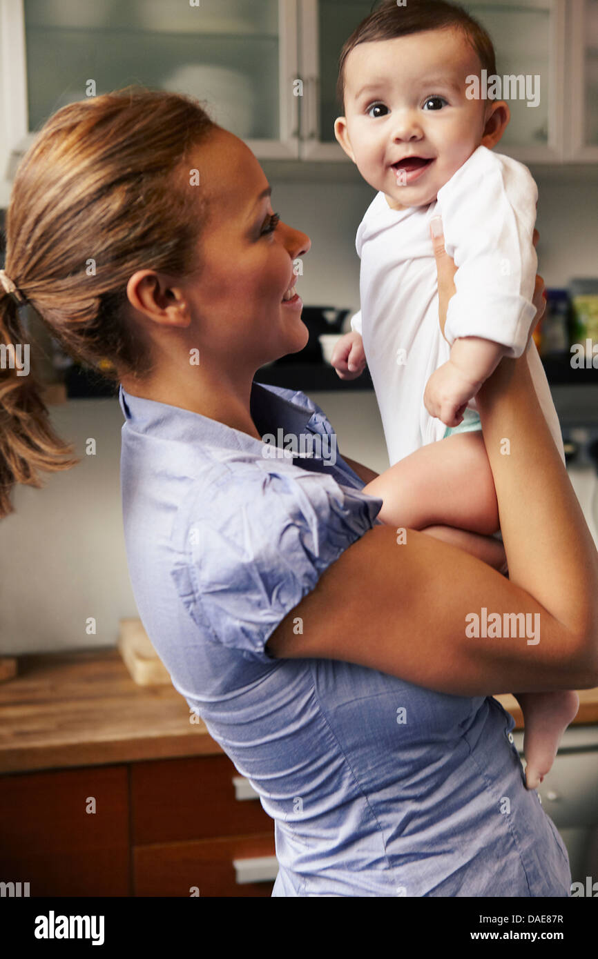 Mother holding baby girl, smiling - Stock Image