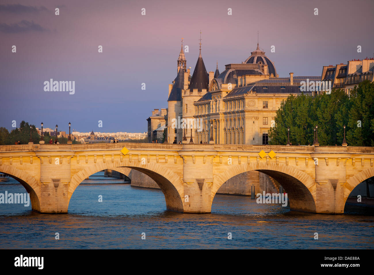 Setting sunlight over River Seine, Pont Neuf and the Conciergerie, Paris France - Stock Image