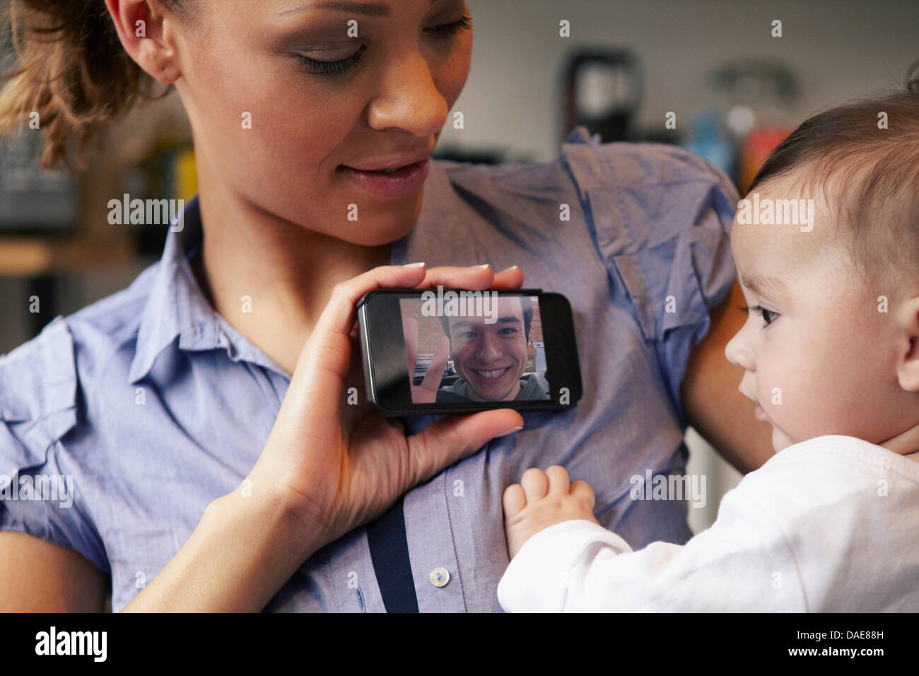 Baby girl watching father on video call, mother holding smartphone - Stock Image