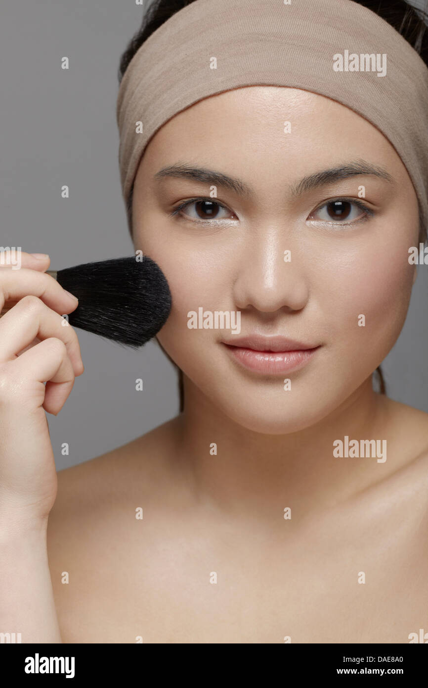 Young woman applying blusher - Stock Image