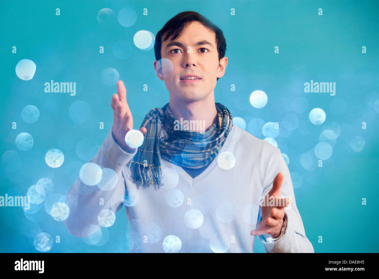 Portrait of young man wearing blue jumper and scarf Stock Photo