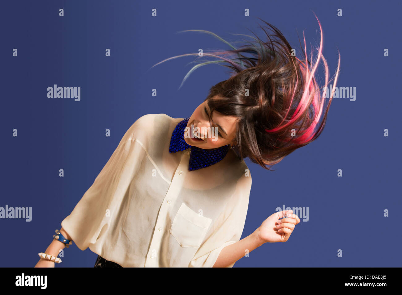 Portrait of young woman with dyed hair dancing - Stock Image