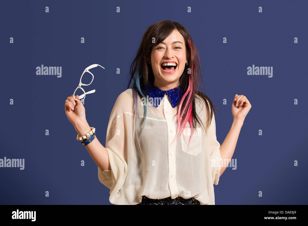 Portrait of young woman with dyed hair holding glasses - Stock Image