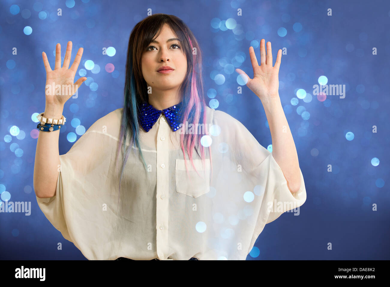 Portrait of young woman with arms up looking at glitter - Stock Image