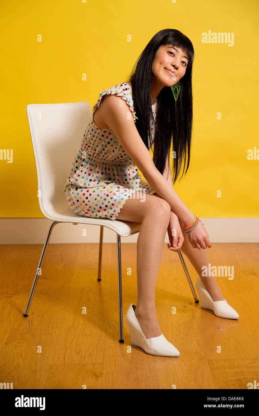 Portrait of young woman wearing spotted dress sitting on chair - Stock Image