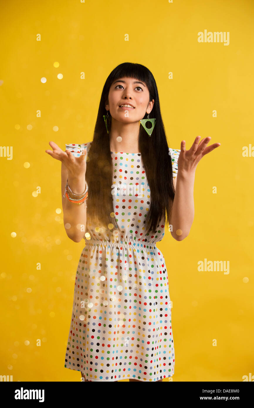 Portrait of young woman wearing spotted dress catching glitter - Stock Image