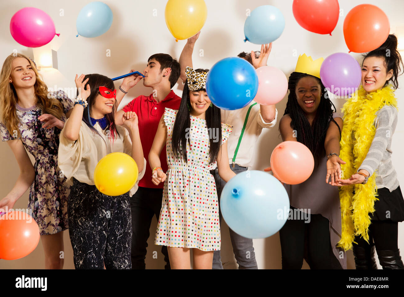 Friends at a party with balloons, studio shot - Stock Image