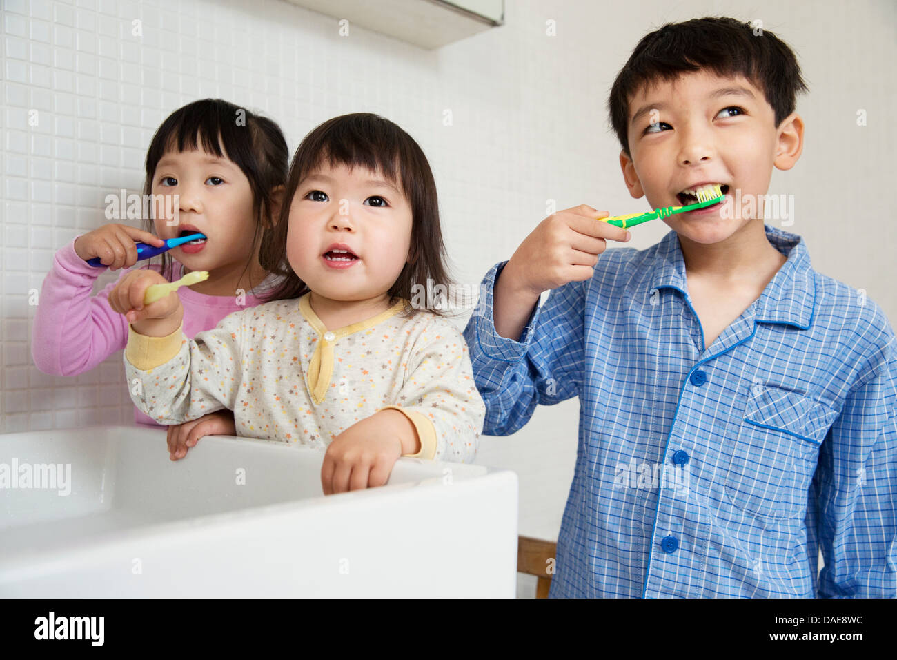 Brother and sisters cleaning teeth - Stock Image
