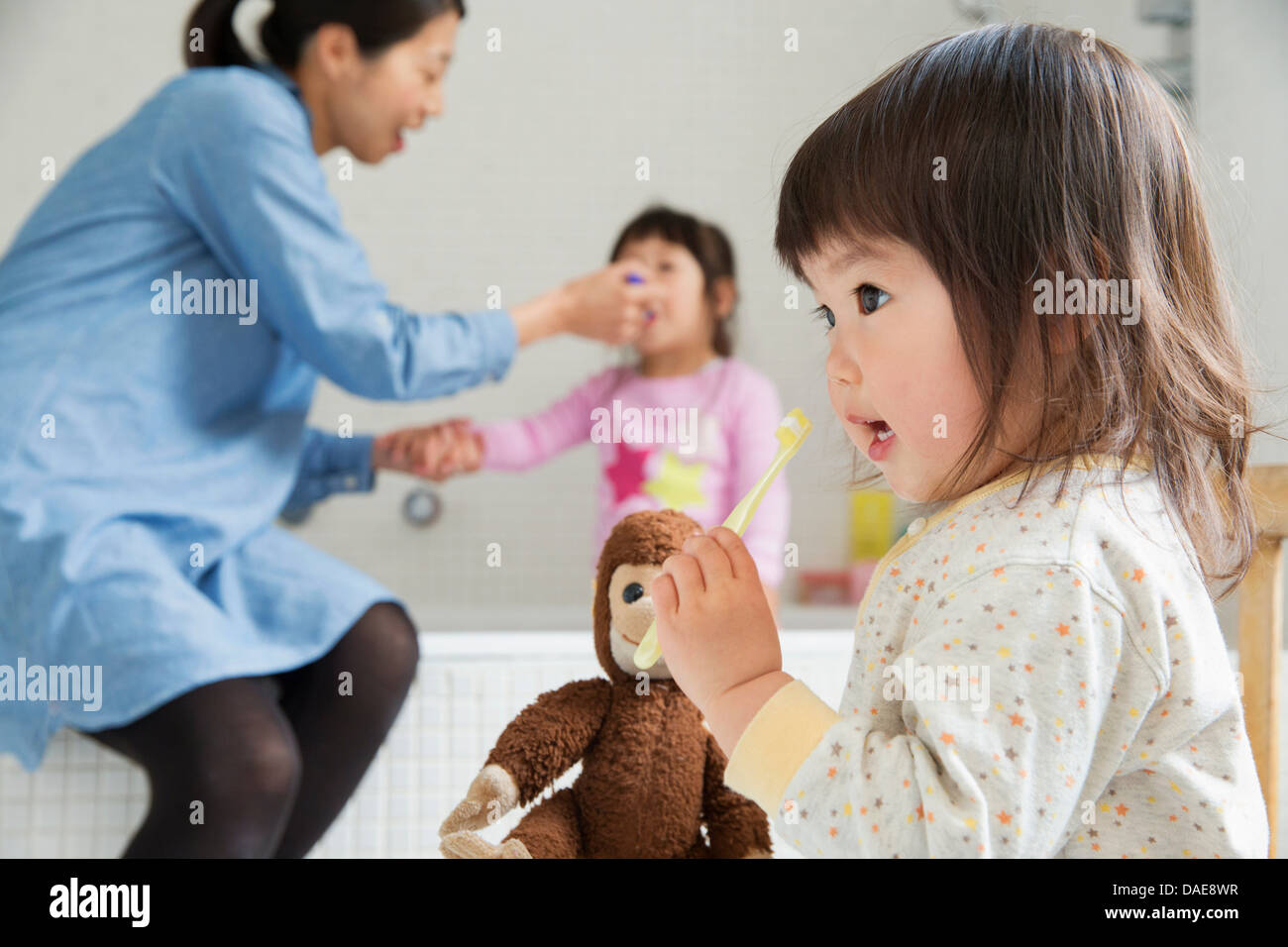 Female toddler with cuddly toy and toothbrush - Stock Image