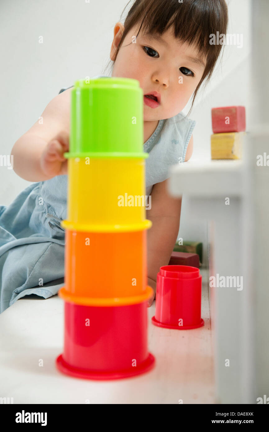 Female toddler on stairs building colorful tower - Stock Image