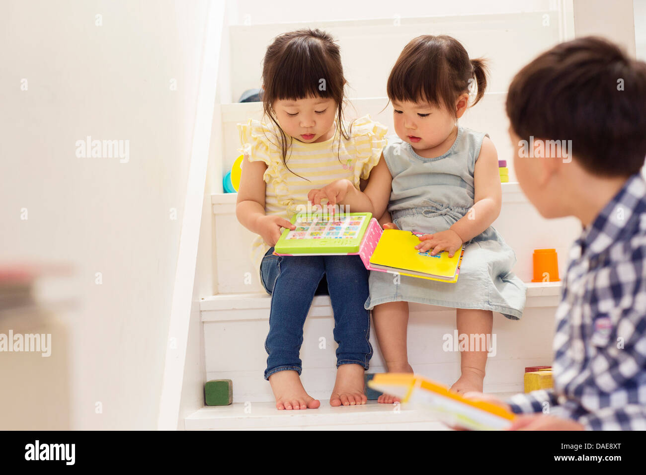 Female toddlers on stairs with game book - Stock Image