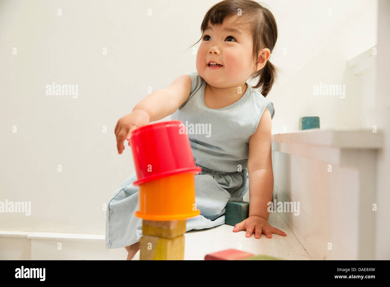 Female toddler on stairs building tower - Stock Image
